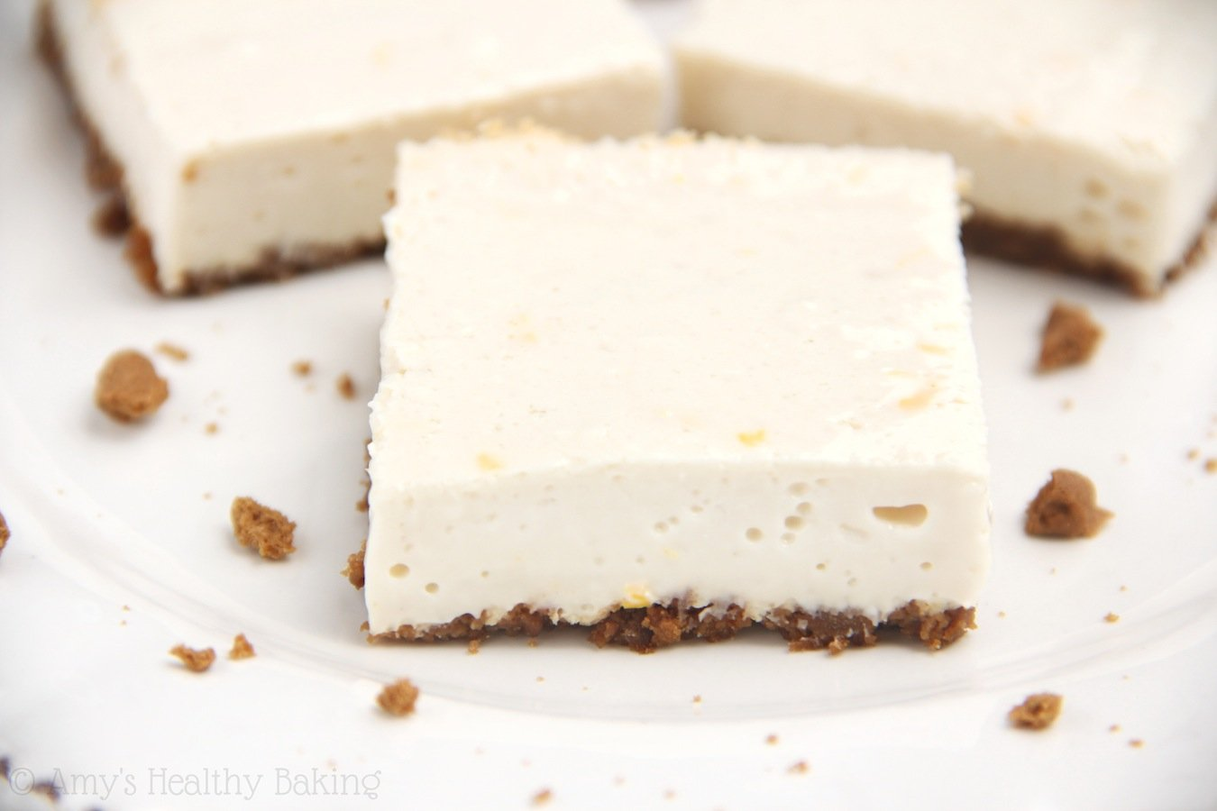 Skinny Lemon Gingersnap Cheesecake Bars -- smooth, creamy & packed with protein. Barely 100 calories each!