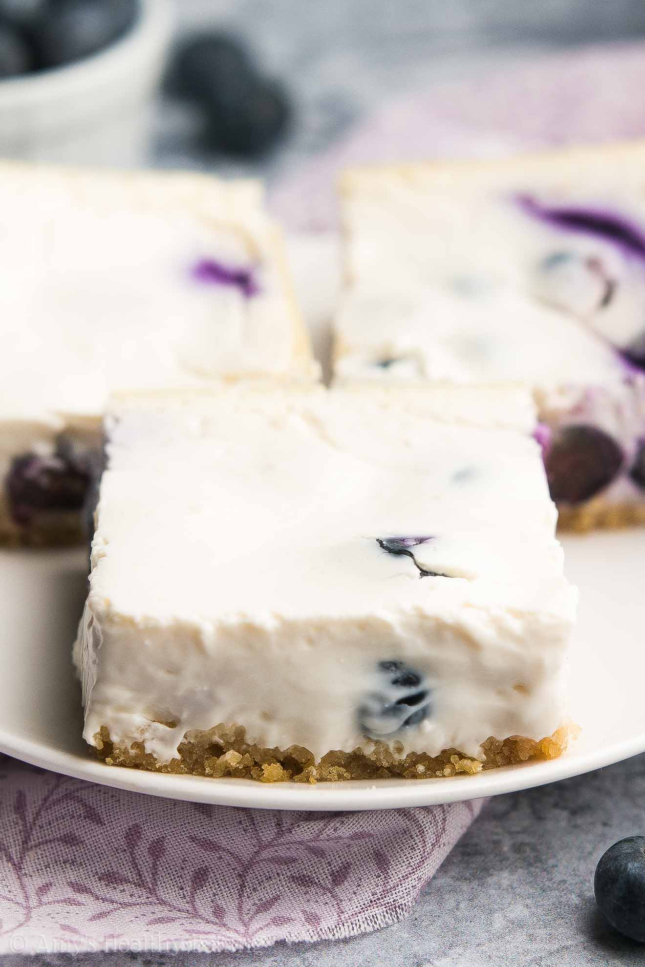 {HEALTHY!} Blueberry Cheesecake Bars -- sweet, creamy & only 63 calories! This recipe is INCREDIBLE!