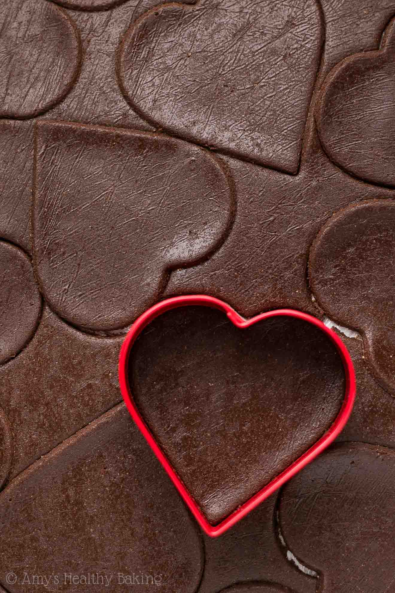 Chocolate sugar cookie dough that's been rolled out and cut into heart shapes with a red cookie cutter