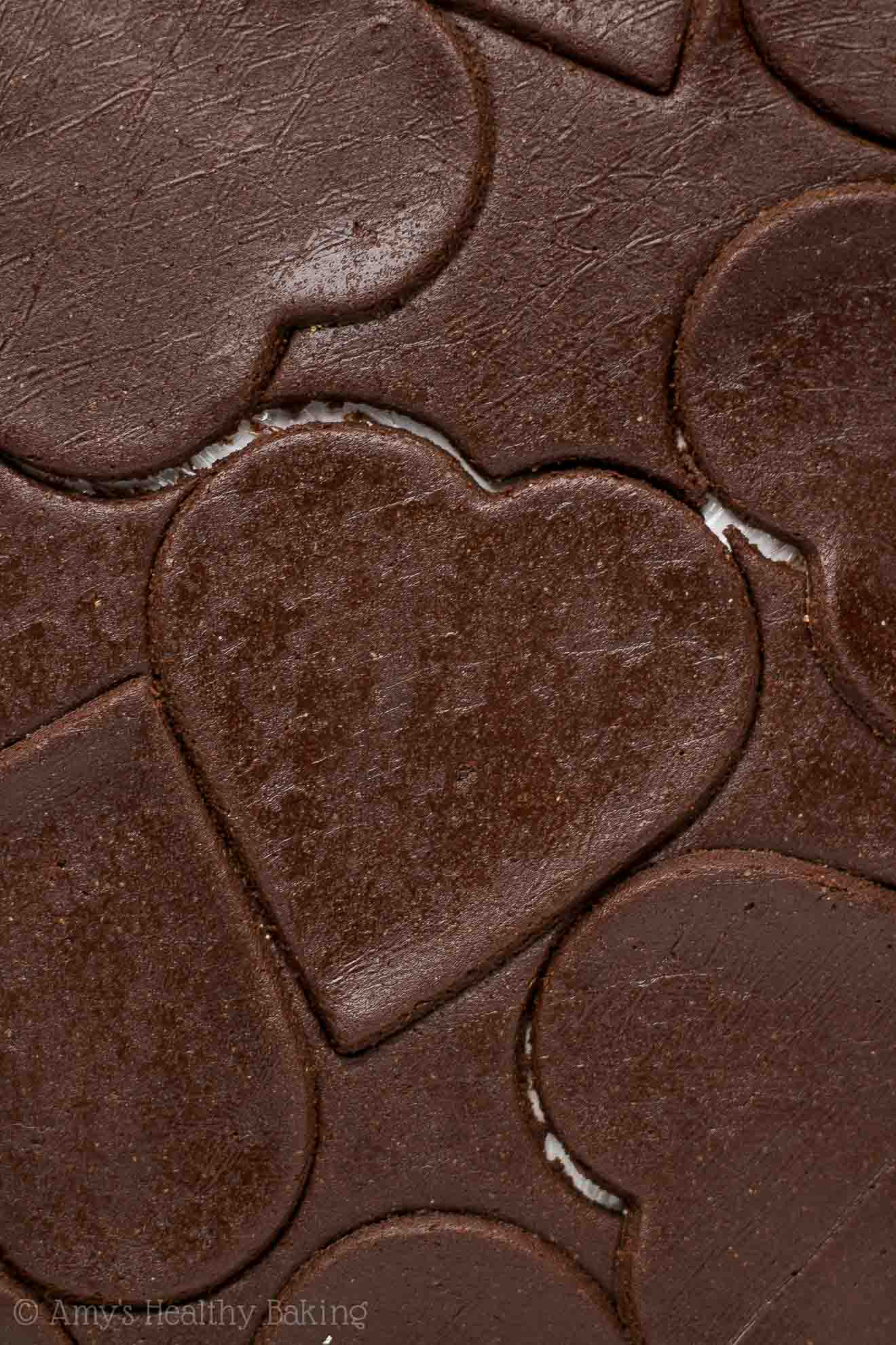 Dark chocolate sugar cookie dough that's been rolled out and cut into heart shapes