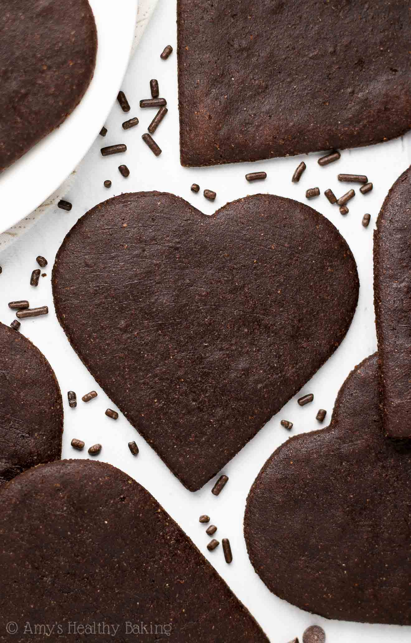 Overhead picture of soft heart-shaped dark chocolate sugar cookies surrounded by chocolate sprinkles
