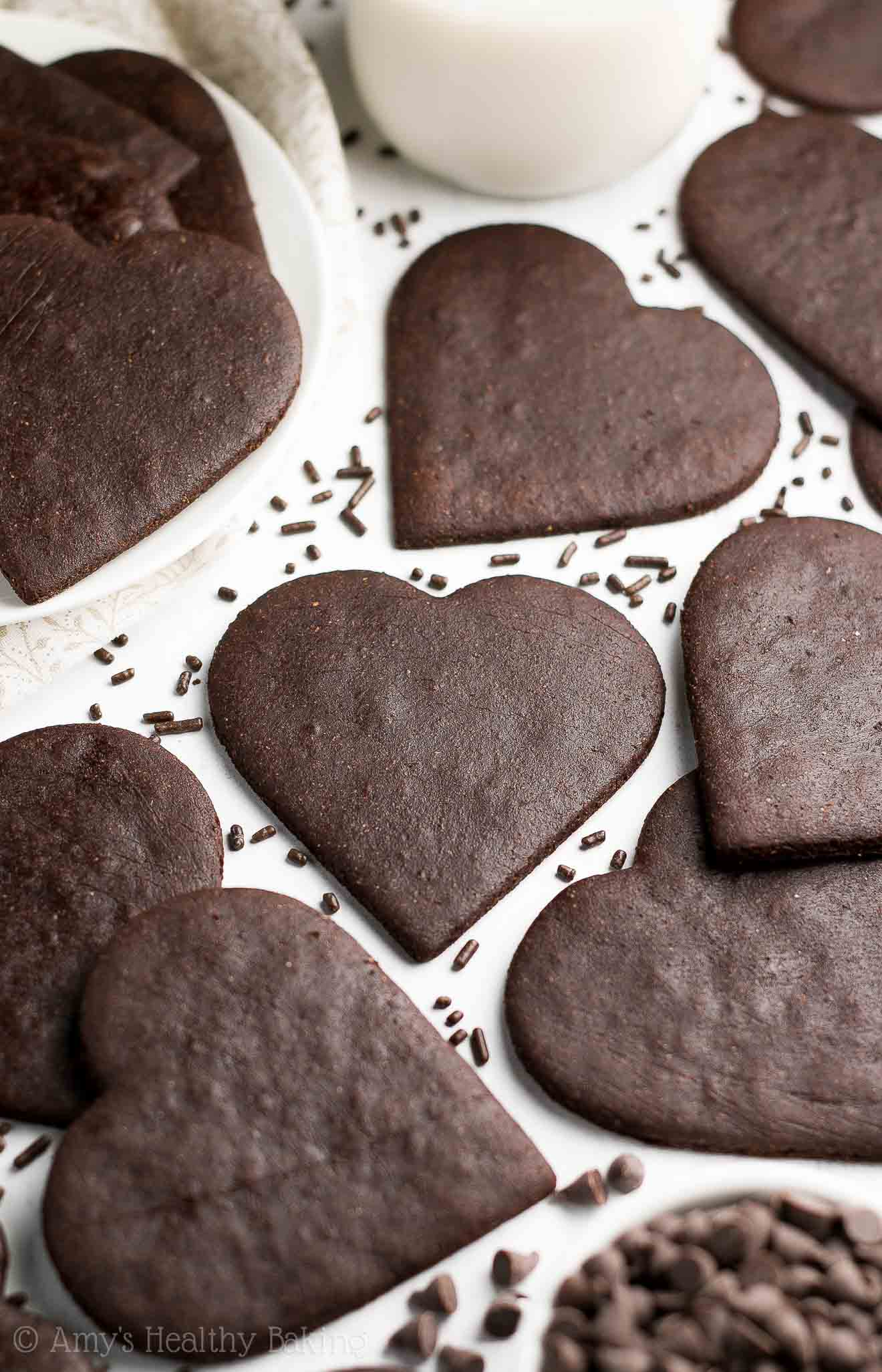 The Ultimate Healthy Chocolate Sugar Cookies - heart-shaped cookies surrounded by chocolate sprinkles