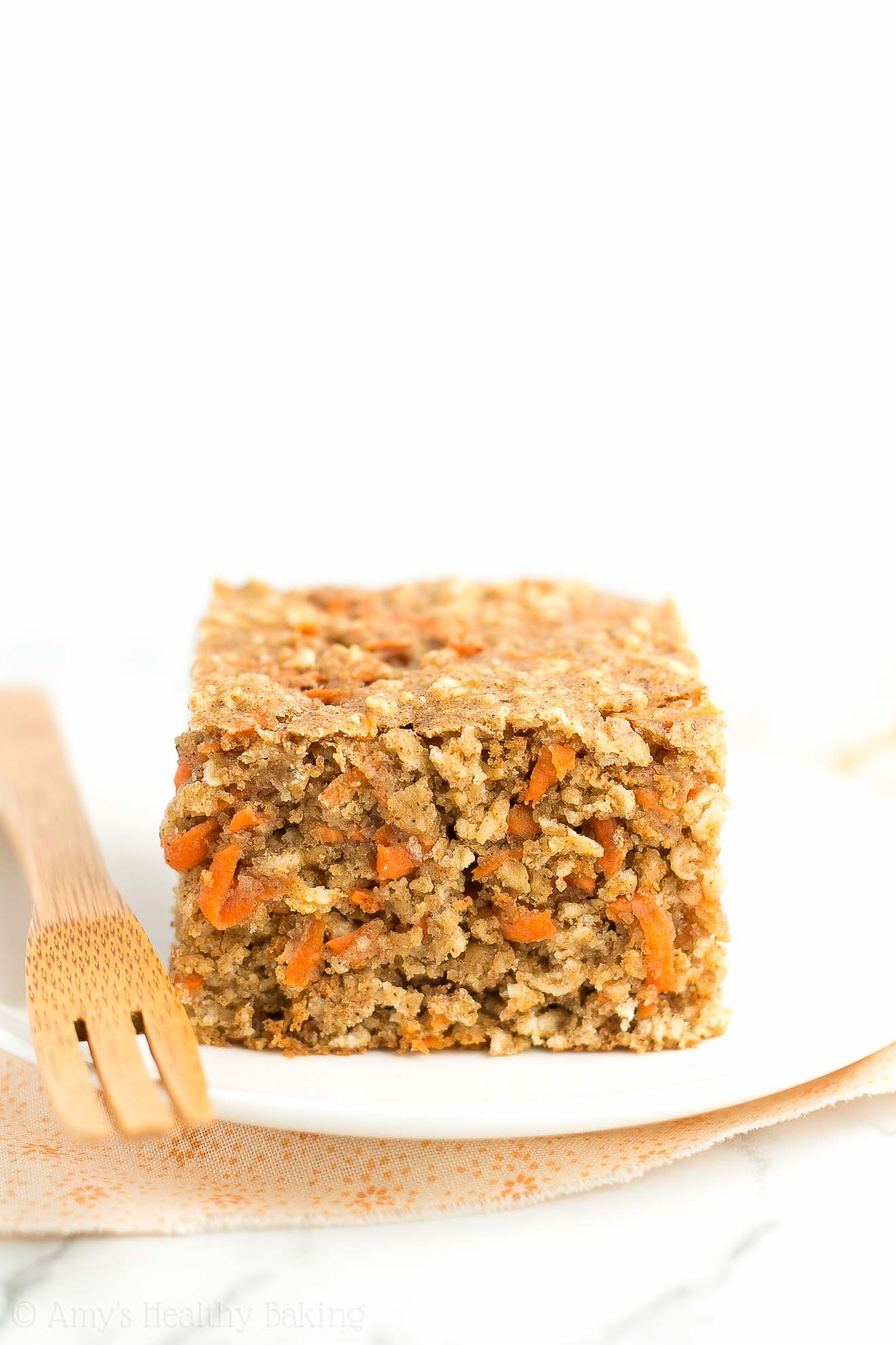 A plate with a fork and a slice of Healthy Carrot Cake Oatmeal Snack Cake