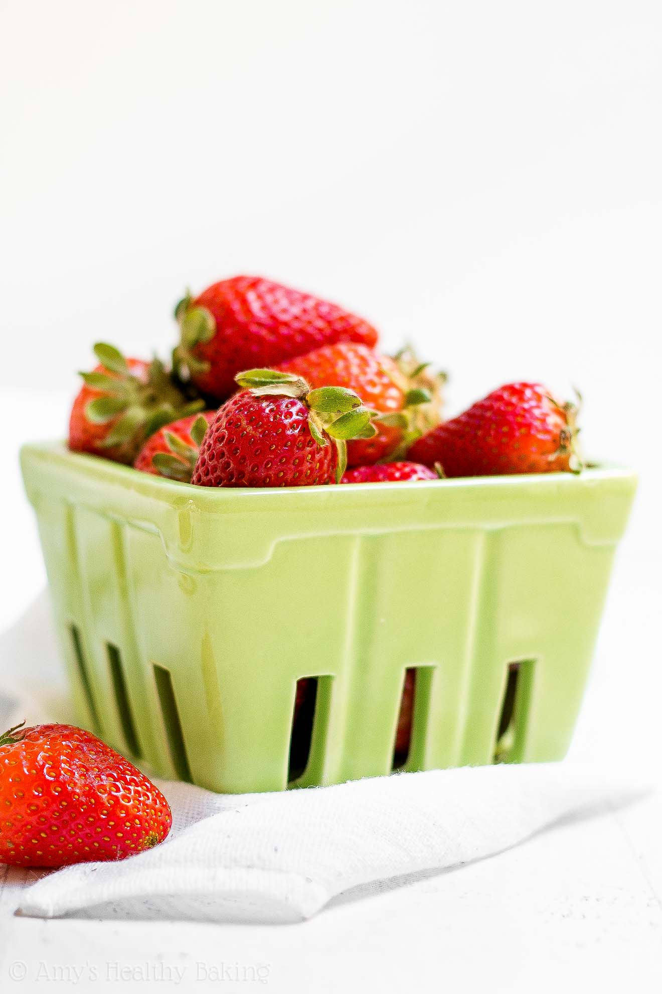 Fresh strawberries in a green ceramic container
