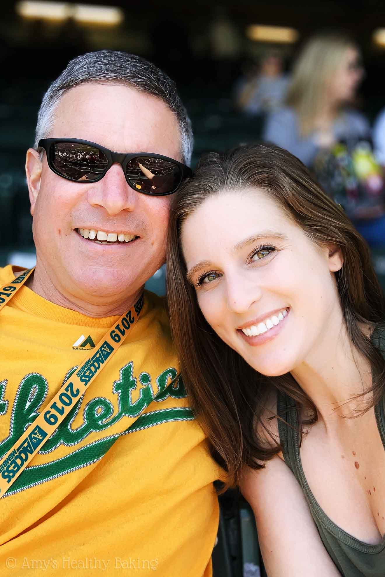 A dad and his young adult daughter at an Oakland A's baseball game