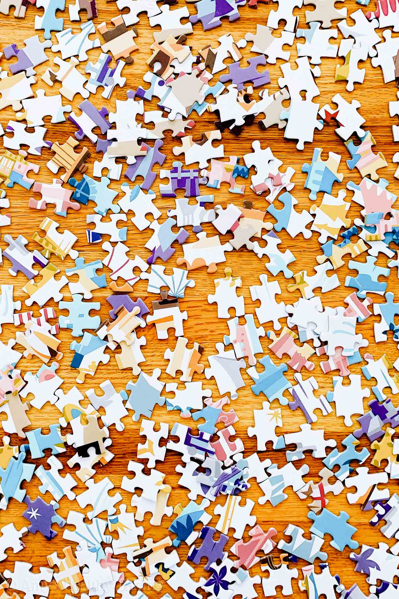 Pastel-colored puzzle pieces on a wooden table