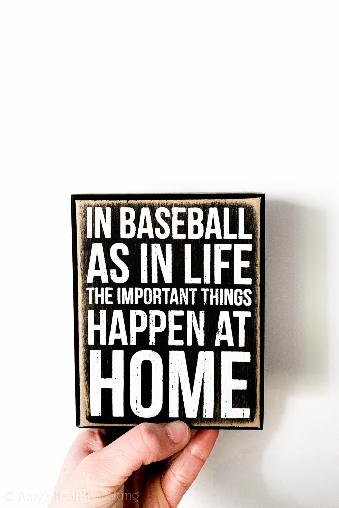 Small black sign: In baseball, as in life, the important things happen at home.