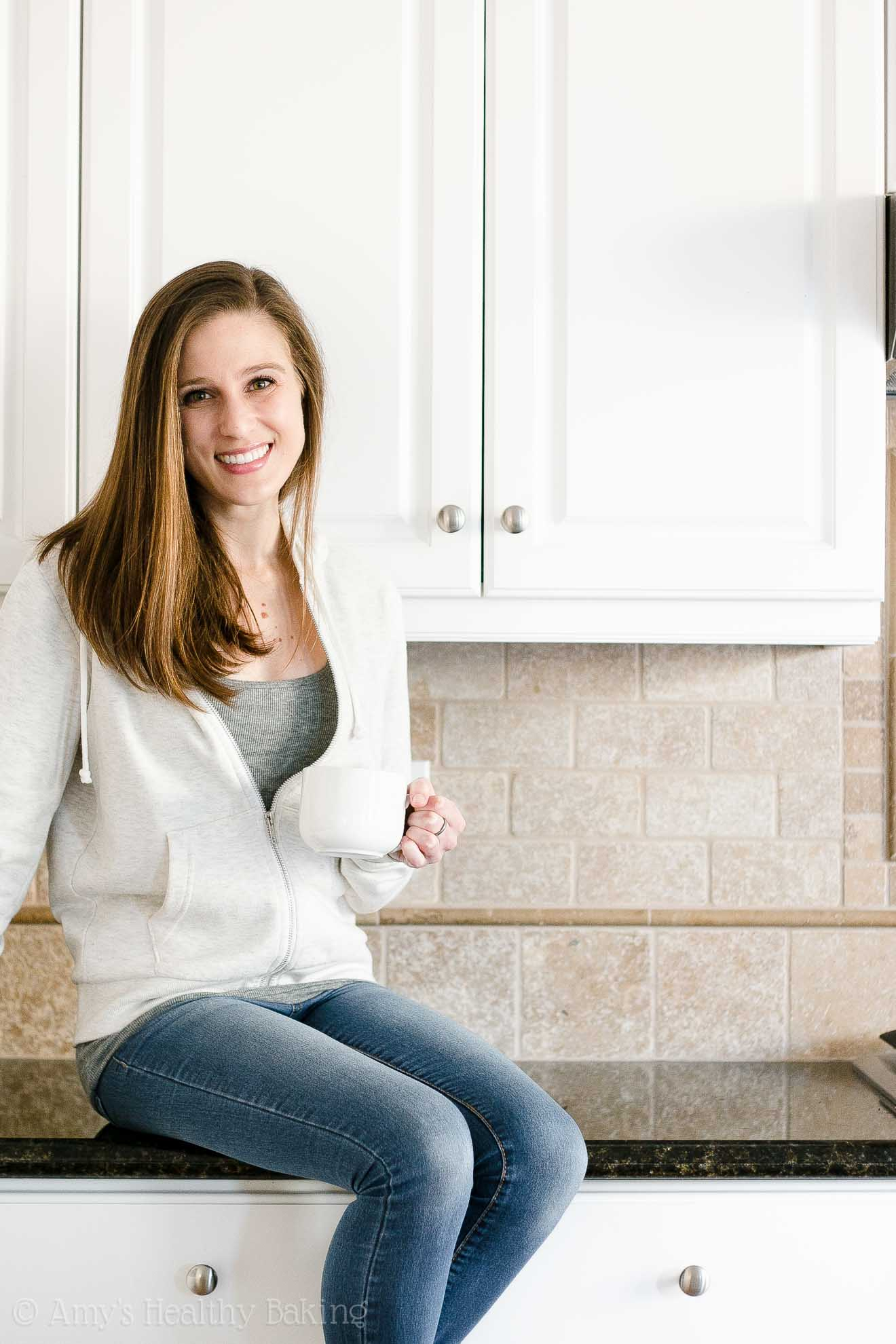 Amy Atherton from Amy's Healthy Baking drinking coffee & sitting on the kitchen counter