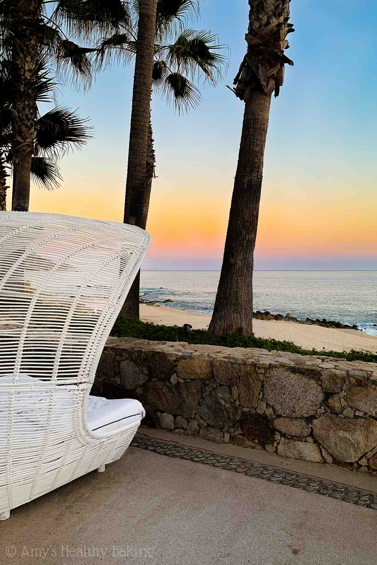 Poolside wicker cabana overlooking a beach at sunset in Los Cabos, Mexico