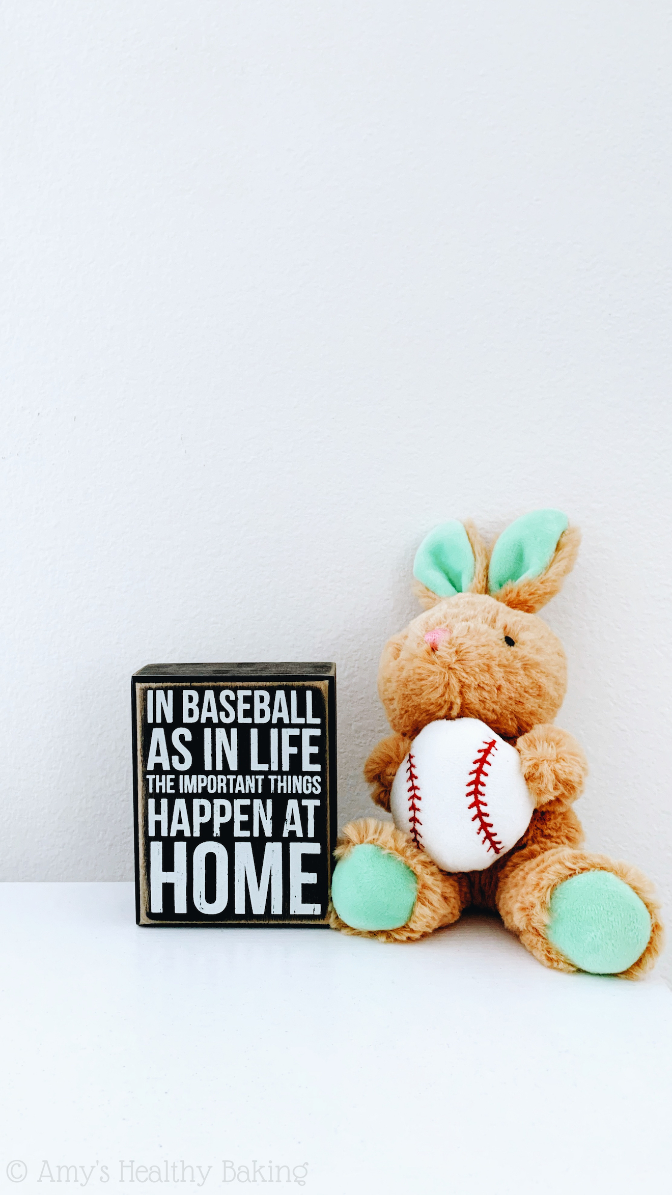 "stuffed rabbit holding a baseball, sitting next to a small wooden sign that reads ""in baseball as in life, the important things happen at home."""
