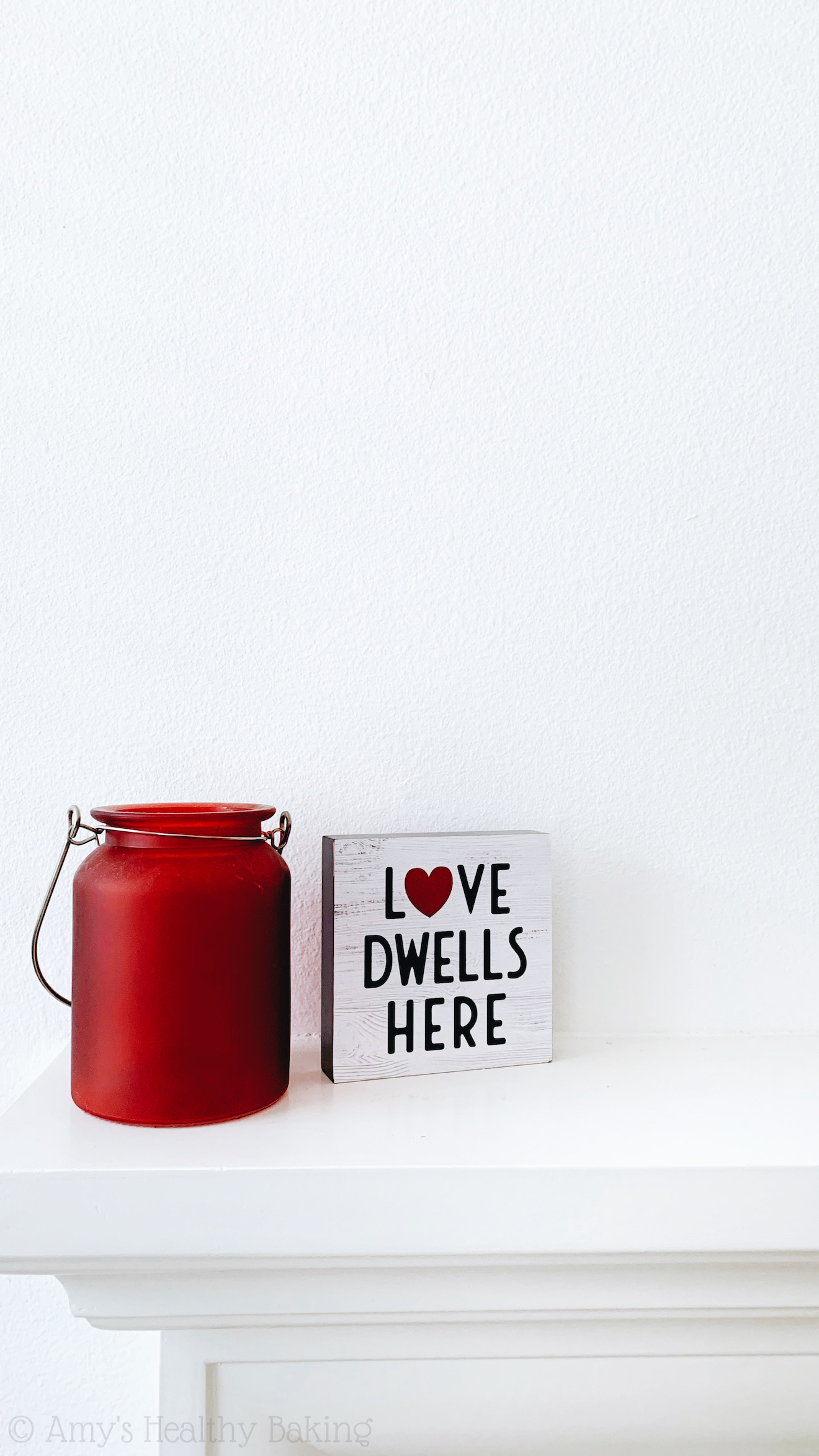 "a red glass jar sitting besides a small wooden sign that reads ""love dwells here"" on a white fireplace mantle"