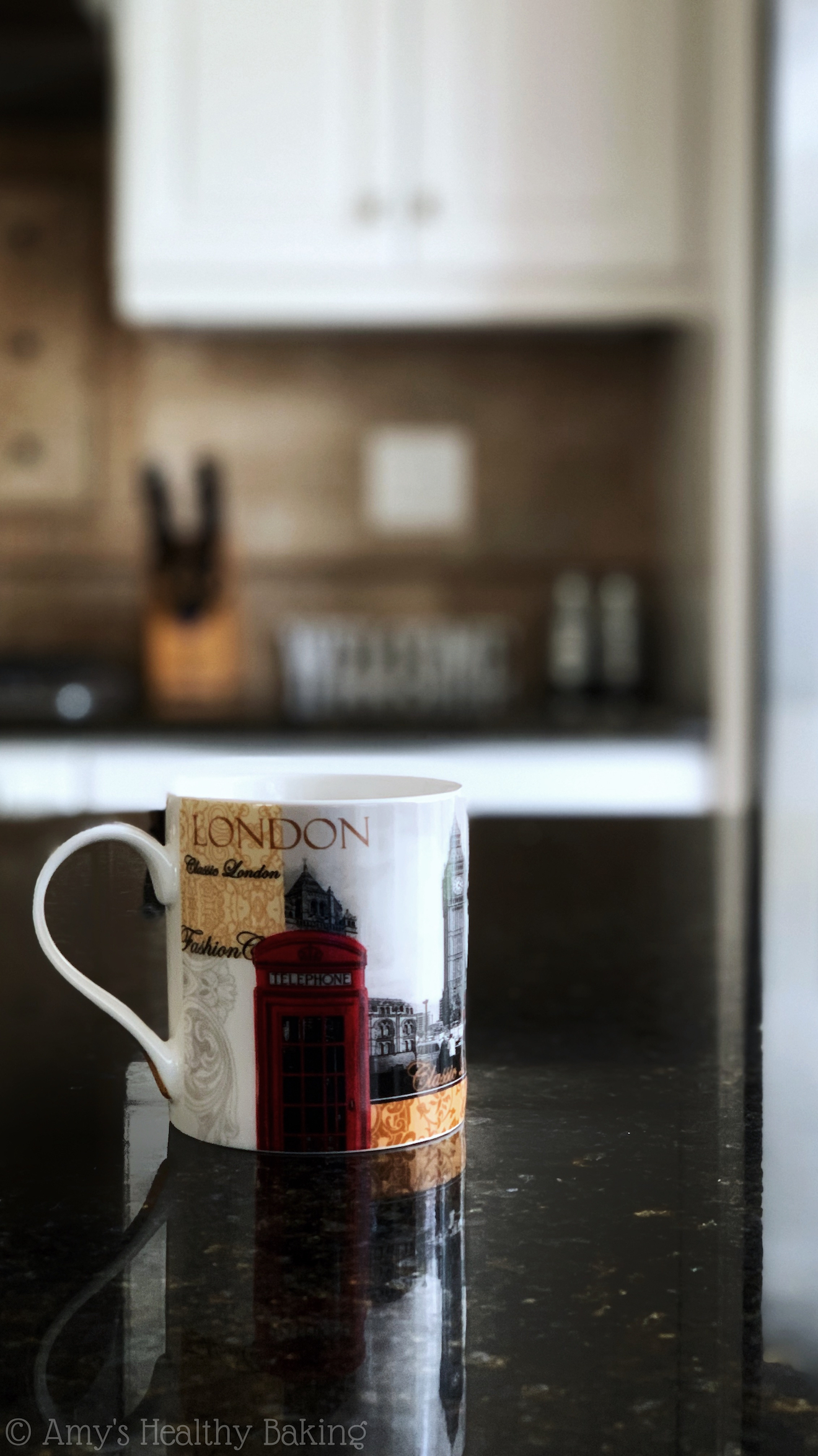 a white coffee mug painted with iconic scenes from London, sitting on a black marble kitchen counter