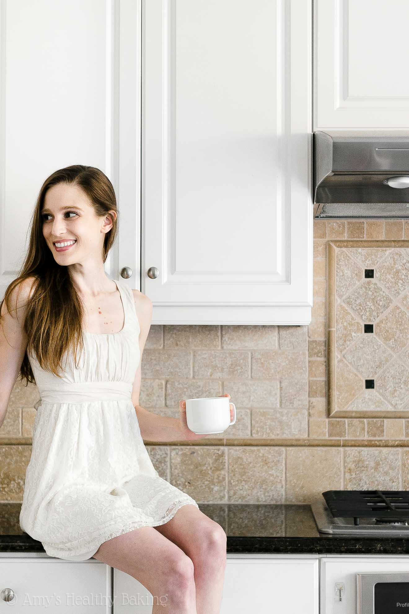 Amy Atherton, founder of Amy's Healthy Baking & intuition coach, sitting on a kitchen countertop