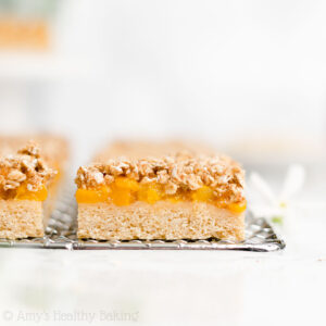 Healthy Peach Crumble Bars – only 79 calories! They taste like peach pie, but they're so much easier to make! (No eggs, dairy, refined flour or sugar too!) ♡ best easy healthy peach crumble bars recipe with gluten free and whole wheat options. low calorie vegan peach oatmeal crumble bars with fresh or canned peaches. clean eating peach dessert recipe.
